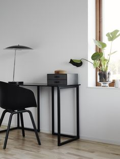 karien anne - minimal workspace / study space - black desk, black chair and black light with a plant in the window