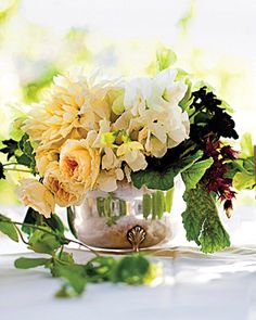 A rustic centerpiece of dahlias, chocolate cosmos, chocolate geraniums, white garden roses, and white sweet peas in a silver vessel