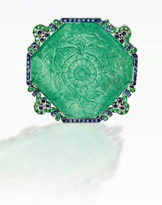Carved emerald brooch, with sapphires, set in platinum. Cartier, c.1920