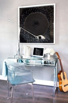 Chic office space with mirrored desk, silver desk lamp, black modern wall art, and a clear armchair.