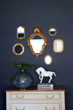 Guest Room: Benjamin Moore Hale Navy paint, gold mirror gallery wall, white horse from Homegoods, glass vessel with leaf, cream and gold dresser with maple top