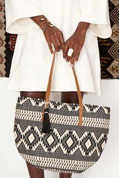 Embroidered tribal-printed,black & white bucket tote with a fun tassel and leather shoulder straps