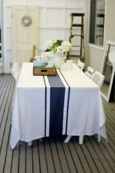 "This table cloth with the single wide dark navy stripe and the pin stripe to either side, a classic but where would you find one?   This one is in Australia from a blog I like called ""Beach Cottage Coastal Decor"""