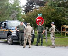 Law enforcement officers stand along a road as the search for two escaped prisoners from Clinton Correctional Facility in Dannemora continues, on Monday, June 22, 2015, in Mountain View, N.Y.  - © AP Photo/Mike Groll