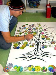 John DeFaro placing the children's colored leaves on the tree.