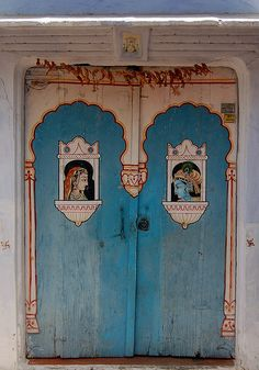 incredibly charming blue doors bearing portraits of Krishna and Radharani gazing at each other lovingly, topped by a small icon of Ganesh - Udaipur, India