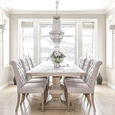 What an awesome dining room! Love the pale grey colors with all the natural light, and that chandelier is just amazing! Such a great place to have a meal with friends!