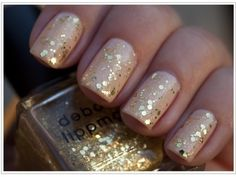 Gold sparkles over pale pink nail polish