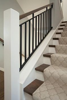 Wood and iron staircase is lined with a gray Moroccan tiles stair runner.