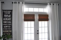 these window treatments exactly: bamboo shade, breezy white curtain panels, iron curtain rods
