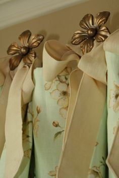 I would use antique drawer knobs or reproductions and attach the drapery with clip rings instead of bows.