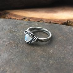 This wire wrap ring contains a gorgeous rainbow moonstone cabochon that has been wrapped in sterling silver and fine silver. This moonstone ring has been oxidized and polished to highlight the detailed wirework. This ring is a U.S. size 8.5 Each piece of jewelry I create contains a
