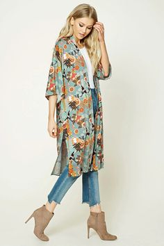 A woven kimono featuring an allover ornate floral and bird print, open-front, 3/4 dolman sleeves, vented sides, and a longline silhouette.