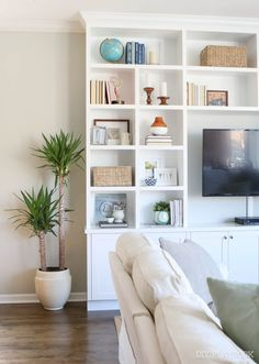 Love these bright white built-ins to hold decor. Takes your eye away from the TV so you can showcase some of your pretty items in your family room space.