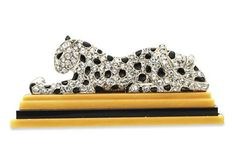 A FINE ART DECO DIAMOND, ENAMEL AND AGATE BROOCH, BY CARTIER   The sculpted rose-cut diamond panther, with black enamel spots, reclining on an agate and onyx platform, mounted in platinum, circa 1928, with French assay marks  Signed Cartier, Paris