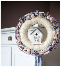 Wianek z kremowego sizalu udekorowany został oplotami w kolorze kremowym oraz fioletowym. Elementem dekoracyjnym jest centralnie umieszczony drewniany domek i ozdoby przyczepione dookoła wianka takie jak : - kremowe kwiatki sola - fiolletowe, drobne kwiatki - muszelki - fioletowe kul...