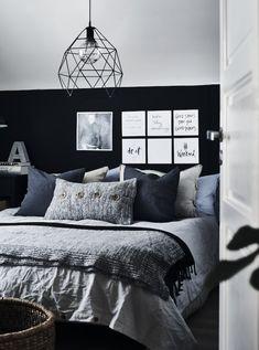Et soverom innredet i grått, svart og blått.
