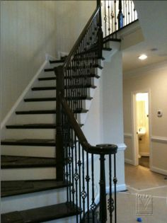 wrought iron baluster in a pewter color with wood handle, fewer decorative items; wood turnstiles