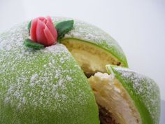 Swedish Princess Cake - made of layers of sponge cake, raspberry jam, vanilla pastry cream, and a dome of whipped cream covered with a thin layer of green marzipan and decorated with a rose (also marzipan)