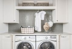 Gray and white laundry room is fitted with a drying rod fixed beneath a shelf mounted to gray grid backsplash tiles between white shaker cabinets.