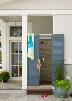 Forget the exposed plumbing and loose gravel underfoot this outdoor shower by Our Town Plans includes wood floors, stone siding, and pretty blue shutters. Perfect for balmy Summer nights. Source: Tria Giovan for Coastal Living Outdoor Bathrooms, Outdoor Baths, Beach Cottage Style, Beach House, Coastal Style, Coastal Decor, Coastal Rugs, Coastal Furniture, Coastal Homes