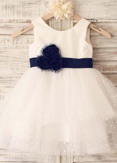 The dress is made of high quality cotton and tulle fabric.It features the dots tulle cupcake skirt and lovely handmade flower sash.The flower is made of navy blue cotton and added the navy blue tulle to help making the shape.We just used a simple hidden zipper to close the back.It is perfect for wed