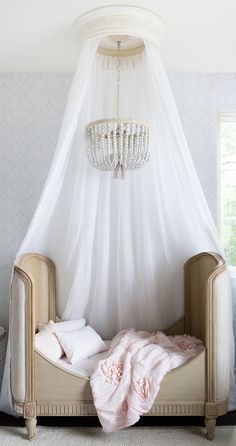 canopy bed & chandelier // little girls' pink & white bedroom
