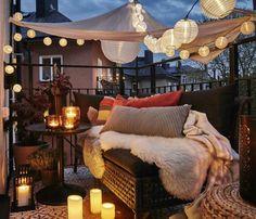 balkon ideen flechtcouch schlafdecke musterkissen musterteppich runder tisch kerzen indirektes licht