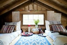 """Without the ceiling, it was like, 'Wow!'?"" explains Sheri. ""We capitalized on all that extra height by putting in a sleeping loft."" The futons up there wear vintage plaid wool throw pillows, plus orange-striped alpaca by D. Bryant Archie. The blue-striped coverlets are from Coyuchi, the chevron runner by Madeline Weinrib. Bright idea: Declare your pride of place by turning state maps into artwork."
