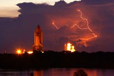 The space shuttle Discovery rolls out to Launch Pad 39A with lightning in the area