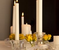 BY EVENT SCENE ADELAIDE. The candles are the feature in this arrangement. But the small bud vases of yellow rose buds brings a splash of colour.