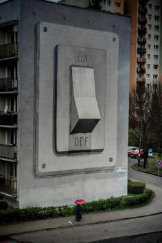 The world is ON! This is a gigantic light switch, a piece of urban art.  See the person at the foot of it?