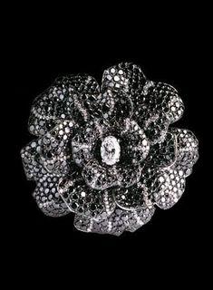Chanel.. Broche Camelia en or blanc 18 carats , 992 diamants noirs pour un poids total de 54,5 carats et 171 diamants blancs pour un total de 4,5 carats dont un diamant central ovale de 2,5 carats