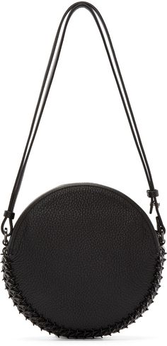 Circular grained leather shoulder bag in black. Single shoulder strap. Accent hardware at perimeter. Zip closure at main compartment. Zip pocket at interior. Tonal stitching. Approx. 7.5