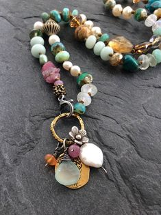 Charm boho necklace - knotted multi charm necklace, multi colour necklace, layering OOAK necklace, bohemian chic by Mollymoojewels Colorful multi charm necklace by mollymoojewels. A mix of semi precious beads, including moonstones, pearls, turquoise, amazonite, jasper, raw ruby, sapphires and Czech glass in hues of blue, Aqua and pink. Adorned with sterling silver accents, a sterling flower charm, an artisan bronze replica of an ancient coin and wire wrapped briolettes The necklace is…