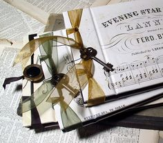 secretleaves paperworks |  Ephemera albums ribbon stab binding - Albums are sheathed in old sheet music and embellished with vintage buttons and keys.