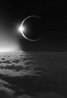 Eclipse. Moon over clouds. Black and white.