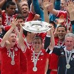 Philipp Lahm of FC Bayern Muenchen lifts the Bundesliga trophy