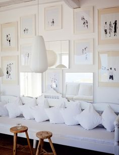 mirrors + matted portraits + white sofa with pillows.  Le salon - Marie Claire Maison