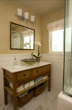 Bathroom. A casually elegant guest bathroom featuring a vanity made from a Chinese cabinet, topped with Calacutta marble and an ocean inspired vessel sink. Vinyl grasscloth wallcovering lend a relaxed feeling. The floor features