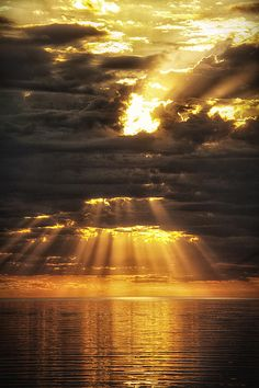 I watched as the golden rays of sunlight shone down from the heavens illuminating the glittering water below.