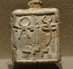 Poids carré en plomb, marqué de symboles divins dont celui de Tanit, Arwad ve ‑ iie siècle av. J.‑C, musée du Louvre.