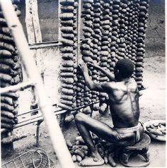 """ukpuru: """" """" Photo of an Igbo man tieing yams onto a large frame made of stakes inside a yam barn. Man wearing loincloth, sitting on a carved stool. """" — J Stöcker, """" Gelatin Silver Print, Large Frames, Knowledge And Wisdom, Outdoor Settings, Falling Apart, West Africa, British Museum, Old Pictures, Black History"""