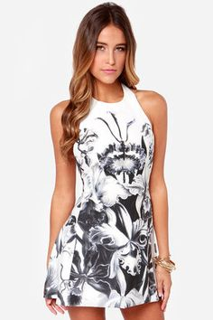 "More than just wishful thinking, the Iris I May Black and Ivory Floral Print Dress is a dream come true! A bold iris print on ivory woven material makes an artful statement on the traditional floral print, while a sexy halter neck bodice slinks into a backless cut and a flared high-low skirt. Neckline fastens with two rounded button at back. Hidden back zipper. Fully lined in ivory woven material. Model is 5'8"" and is wearing a size small. Dress measures 4"" longer at back. 100% Cotton…"