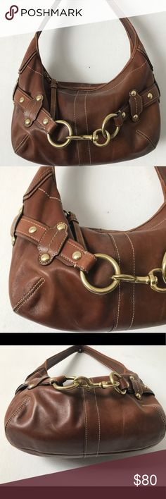 """Coach Hampton Ergo Shoulder Bag Coach Hampton Ergo Leather Belted Hobo shoulder bag #11261. Excellent condition!  Leather is in excellent condition with no stains. Coach Hang tag missing. Interior has a small stain on one end, otherwise very clean.   Brown Leather  * Leather Belted Strap with studs and dog leash clip  * Zip top closer  * Interior zippered pocket  * Two Interior multi-function pockets  * Measures: 14"""" (L) x 9""""(H) x 3"""" (W)  * 7"""" Drop Handle  * Brass hardware  * Coach leather…"""