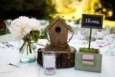 I love this centerpiece idea: cut a tree stump, put a cute birdhouse on the top, use a vintage wooden box or a flowerpot to place moss and table number in, and place a mason jar full of fresh cut flowers next to it all.