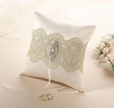 """This beautiful vintage inspired gold lace ring pillow features ivory satin and a band of gold lace adorned with a rhinestone/pearl decoration. It measures 7""""."""