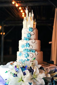 3-tier wedding cake, Disney-inspired with fondant, blue floral accent, topped with a Disney castle.