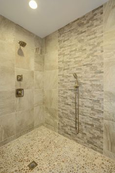 This Spacious Master Bathroom Shower Features Three Different Types Of  Natural Stone, Including A Neutral Pebble Tile Floor And Large Square Wall  Tiles.