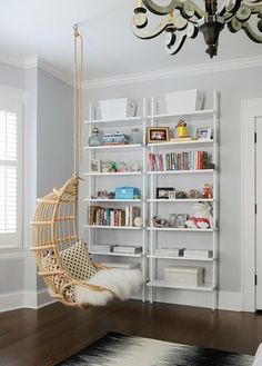 A Twos Company Hanging Rattan Chair hangs over a black and white rug in front of a two side by side white ladder bookshelves positioned in front of light gray walls lined with white crown molding in this stylish, well appointed teen girls bedroom.